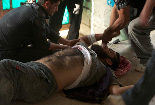 Бойцу оказывают первую помощь при ранении, полученном в третий день боев в Кафр-Зайте. В течение четырех дней правительственные войска сражались с повстанцами за город Кафр-Зайта в Сирии. Бои продемонстрировали, что дезорганизованные оппозиционные войска порой могут выдержать удар профессиональных военных. Фото сделано 4 июня 2012 года.