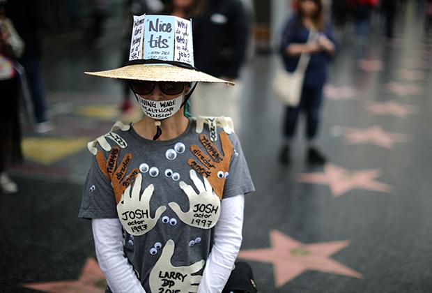 Активистка во время марша протеста против сексуальных домогательств. На ее одежде имена всех людей, которые когда-то ее домогались. Лос-Анджелес, США