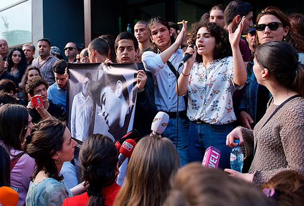 Митингующие у здания прокуратуры держат портреты убитых школьников