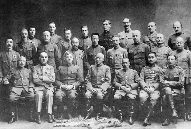 Передний ряд, слева направо: генерал-майор Сабуро Инагаки (японская армия), полковник Луи Гисье (бельгийская армия), генерал-майор Уильям Сидней Гревс (армия США), генерал Кикудзо Отани (японская армия), генерал-лейтенант  Мицуэ Юхи (японская армия), бригадный генерал Юи Мицуэ (японская армия), подполковник  Филиппи, граф Бальдиссеро (итальянская армия).