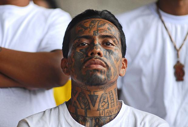 Сальвадорцы принесли свои традиции и в другие преступные группировки. Например, главным врагом MS-13 является мультинациональная банда Mara 18, состоящая из выходцев из Центральной Америки и Мексики. Бандиты с 18-й улицы тоже забивают лицо татуировками. На фото как раз член Mara 18, отбывающий наказание в тюрьме Исалько в Сан-Сальвадоре.