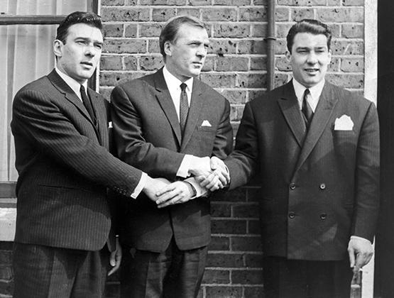 Братья Крэй (Чарли в центре) рядом с домом своей матери. Чарли старался не участвовать в криминальных делах близнецов, но всегда был рядом в трудную минуту и помогал деньгами в начале пути Реджи и Ронни.