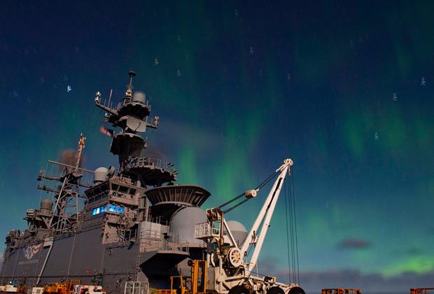Универсальный десантный корабль типа Wasp Военно-морского флота США USS Iwo Jima (LHD-7) на фоне полярного сияния после учений. Два других корабля группы не смогли принять участие в Trident Juncture 2018 — один был поврежден во время шторма у берегов Исландии, после чего второй в качестве меры предосторожности отправили в порт.