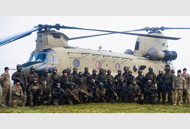 Военнослужащие 12-ой кавалерийской дивизии армии США и немецкого пехотного взвода перед американским тяжелым военно-транспортным вертолетом продольной схемы CH-47 Chinook в городе Рене (Норвегия).