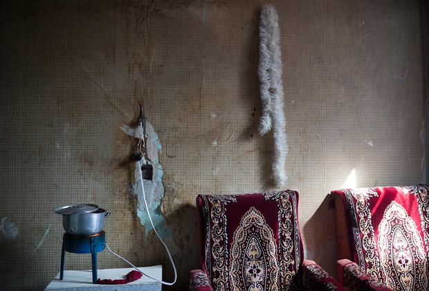 Когда-то в общежитии были общие кухни с газовыми плитами. Сегодня оставшиеся жильцы готовят еду в своих комнатах. В большинстве случаев электроплитка выполняет еще и функцию отопительного прибора. Эта комната одновременно служит кухней, гостиной и детской.