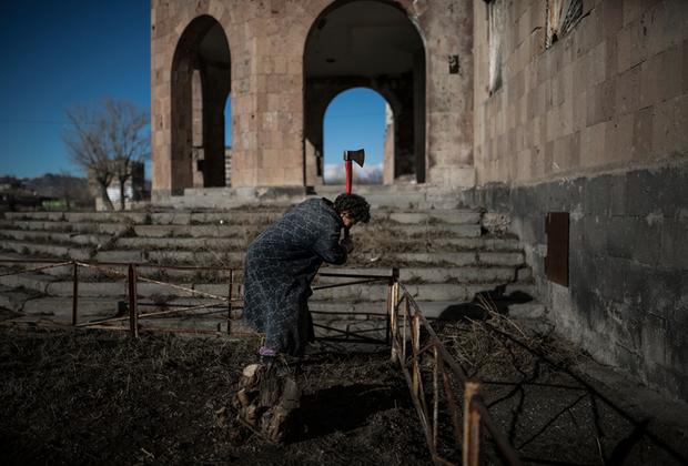 Карине, 57 лет. Она прожила в заброшенном общежитии на окраине Гюмри 26 лет.  По мере сил Карине пытается следить за чистотой во дворе своего дома. Она собирает мусор и вырубает засохшие кусты.