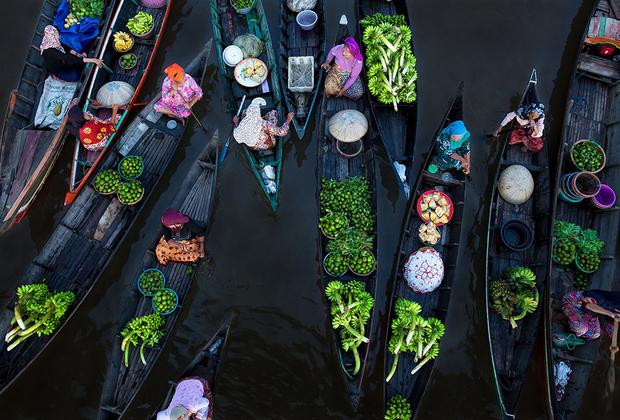 Ранним утром перед восходом солнца на красочном плавучем рынке Lok Baintan в Индонезии встречаются до ста лодок. Это один из старейших рынков в Азии, где жители до сих пор торгуют традиционными деревянными лодками.
