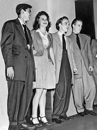 Молодые люди на танцах в одном из отелей Вашингтона, округ Колумбия. В отличие от парней, одетых в зуты, девушки правила не нарушают —у них короткие юбки, на которые ушло не так и много материи. Август 1942 года.