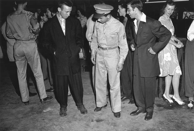 Полицейский осматривает посетителя концерта Оркестра Вуди Хермана, одетого в зут-костюм. Вашингтон, округ Колумбия, июнь 1942 года. На Восточном побережье США белые американцы начали носить костюмы зут раньше, чем на Западном, а Глубокий Юг так и оставался не затронутым этой модой.