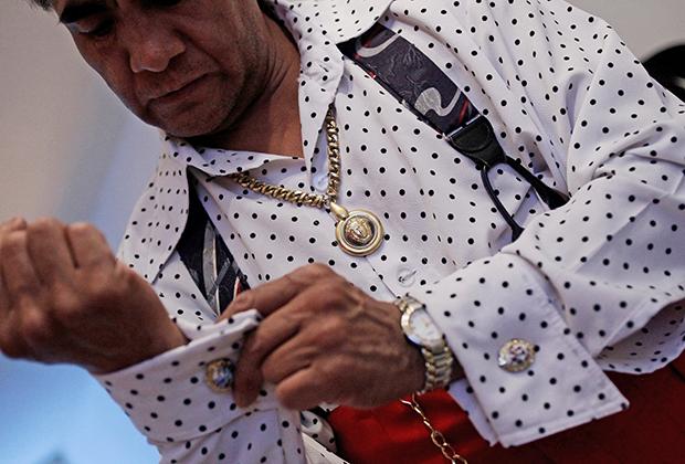 Житель Мехико Даниэль Родригес, одетый в стиле пачукос, позирует на фоне расписанной в традиционном стиле стены в Мехико.