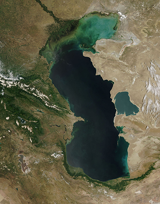 Вид Каспийского моря из космоса. На нем хорошо видно, что в северной части озеро зеленеет из-за водорослей. Дело в том, что соленость Каспия неравномерная: от 0,1 промилле неподалеку от дельты Волги до 11-13 промилле в юго-восточной части озера.