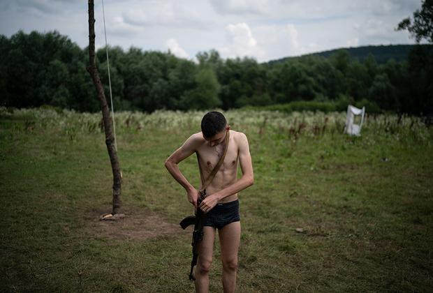 """Подобно воинам прошлого, они спят, едят и отдыхают с оружием под рукой. Так боец всегда готов отразить внезапное нападение. Но такое единение с автоматом приходит не сразу. Воспитатели другого лагеря, полка «Азов», <a href=""""https://lenta.ru/articles/2018/07/03/ukrjugend/"""" target=""""_blank"""">рассказывают</a>, что для некоторых кадетов даже не потерять оружие за две недели уже считается успехом. Впрочем, большинство с этой задачей справляется, а покинув лагерь, первое время просыпаются среди ночи и рефлекторно ищут у кровати свой «калаш»."""