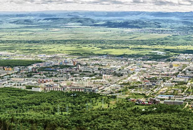 Вид на региональный центр Сахалинской области город Южно-Сахалинск с высоты окрестных сопок. Город отличает низкоэтажная застройка и большой частный сектор.