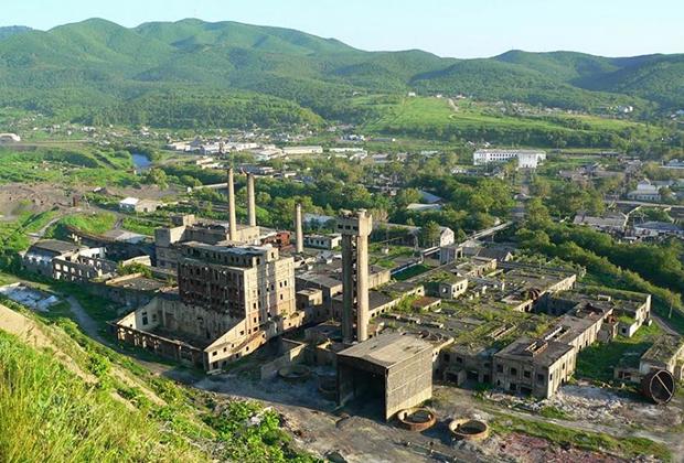 С сопки, на которой расположен храм, открывается вид на бумажный завод, бывший в советские времена градообразующим предприятием. Сейчас от него остались только руины.