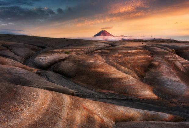 «Раскрашенная пустыня» — еще один кадр от Дилана То. Действующий вулкан Нгаурухоэ виднеется из-за облаков на горизонте, а расположенные на переднем плане скалы находятся в нескольких сотнях метров от Пустынной дороги, ведущей на север в сторону Туранги. Благодарить за буйство красок нужно закат.