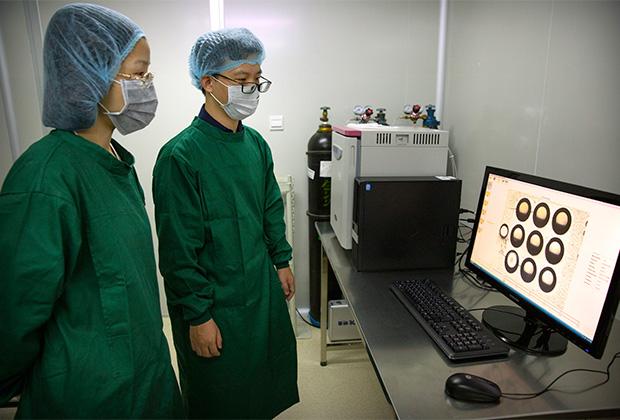Ученые смотрят на изображения эмбриона в лаборатории Хэ Цзянькуя.