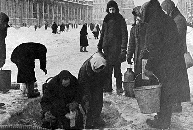 Жители блокадного Ленинграда набирают воду, появившуюся после артобстрела в пробоинах в асфальте на Невском проспекте.