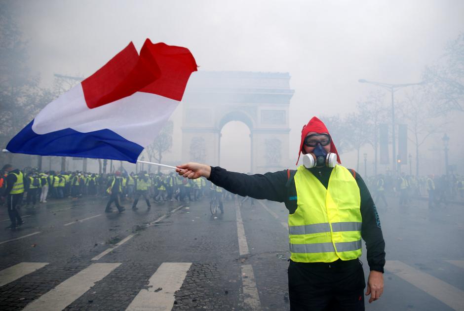 Протестующий размахивает флагом Франции у Триумфальной арки
