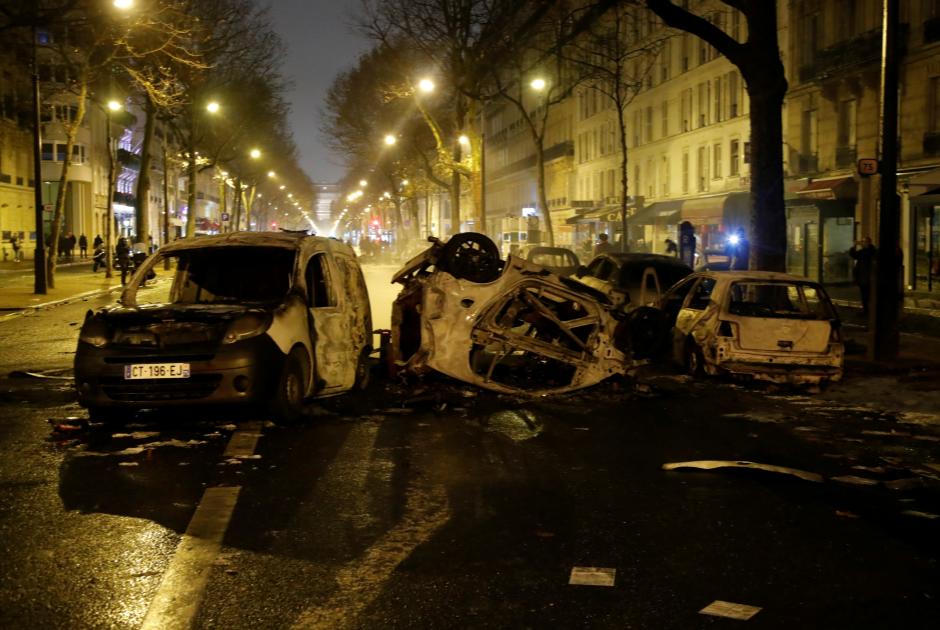 Сожженные полицейские машины на проспекте Клебера в центре Парижа