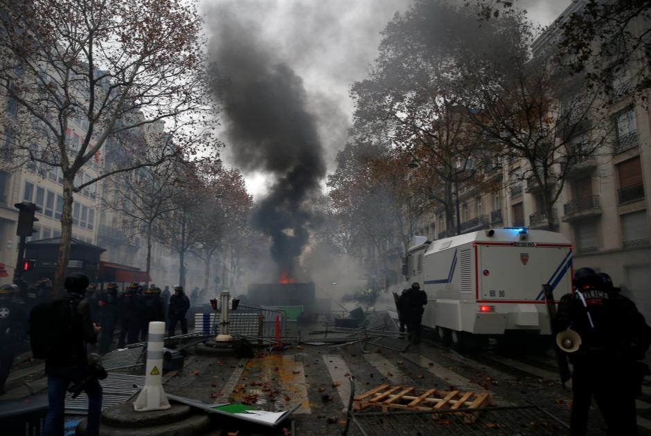 Полицейские рядом с баррикадами на парижской улице
