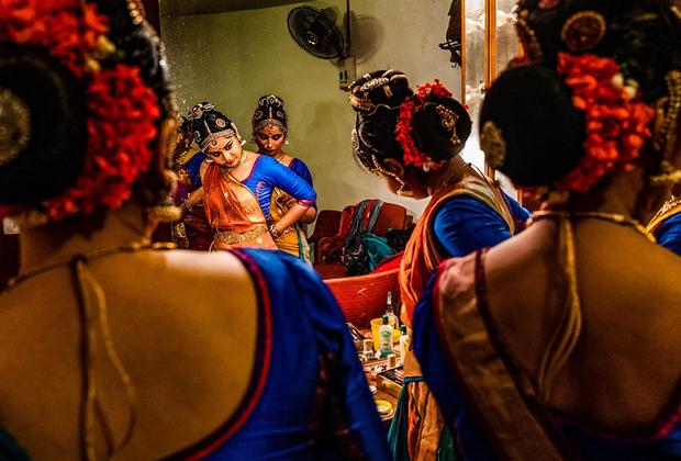 Танцовщицы кучипуди — классического индийского танца — тихо готовятся к выступлению за кулисами. Кучипуди — танец древний (родился еще до нашей эры) и непростой. Он совмещает музыку, поэзию, театральное искусство, немалый упор делается на мимику и жесты.