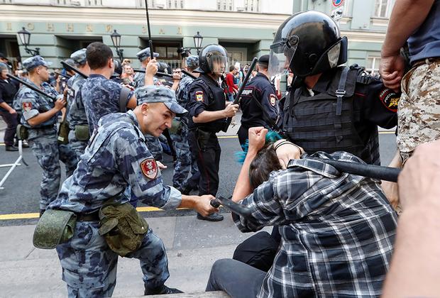 Полицейские бьют протестующего на митинге против запланированного повышения пенсионного возраста.