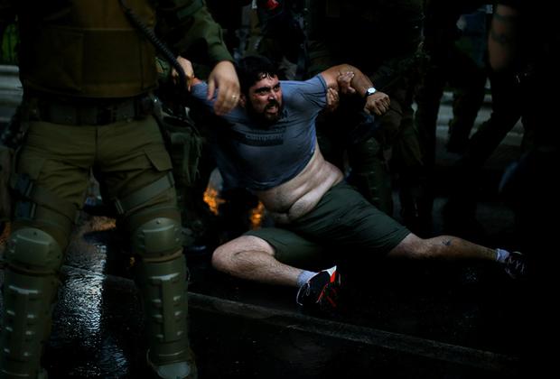 Задержание демонстранта во время акции протеста в столице Чили — Сантьяго. Протестующие требовали положить конец спекуляциям в системе образования.