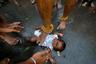Индийский брахман прикасается ногой к ребенку. Таким образом он благословляет малыша во время праздника, посвященного богине-матери Мариамман.