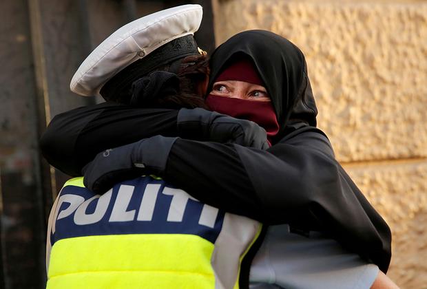 """37-летняя Айя в хиджабе плачет, обнимая полицейского во время демонстрации  против <a href=""""https://lenta.ru/news/2018/05/31/burqa_ban/"""" target=""""_blank"""">запрета</a> на ношение закрывающих лицо никабов в Дании."""