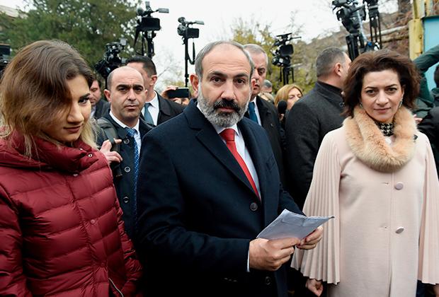 Никол Пашинян, его супруга Анна Акопян (справа) у избирательного участка во время внеочередных выборов в Национальное собрание (парламент) Армении