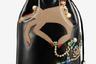Праздничная версия сумки-помпадур Marie Jane украшена стразами и аппликацией: изящная женская ручка держит украшения. При желании даритель может выбрать из нескольких версий сумки ту модель, цвет аппликации на которой идеально совпадает с тоном кожи будущей обладательницы аксессуара.