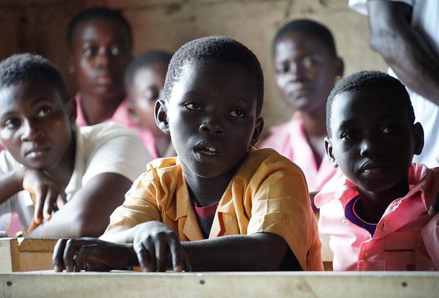 В некоторых деревенских школах учебников и парт хватает не на всех. Поэтому ученики иногда впятером ютятся за деревянными столами, представляющими из себя сколоченные вместе необработанные доски.