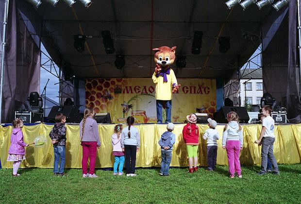 Сандово, Тверская область, август 2015 год. <br> <br> Дети смотрят выступление ростовых кукол на Дне пчелы в Сандово.