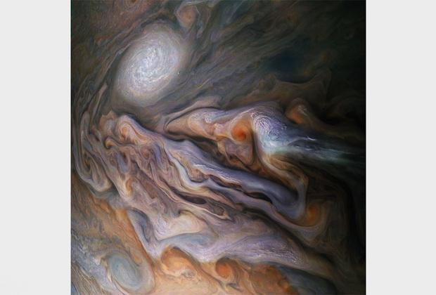Межпланетная станция Juno уже восемь лет изучает Юпитер, получая богатые данные и снимки газового гиганта. Вихрящиеся облака и большой ураган — белый овал на фотографии — располагаются в северном полушарии планеты.