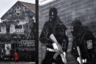Девушка переходит улицу возле граффити, посвященного памяти погибших при крушении «Титаника». На первом плане — военизированная уличная роспись, прославляющая боевиков-лоялистов из группировки «Ольстерские добровольческие силы». Это протестантское объединение, основанное в середине XX века, агрессивно выступало за сохранение Северной Ирландии в составе Великобритании. Основными инструментами их борьбы стали теракты и политические убийства.