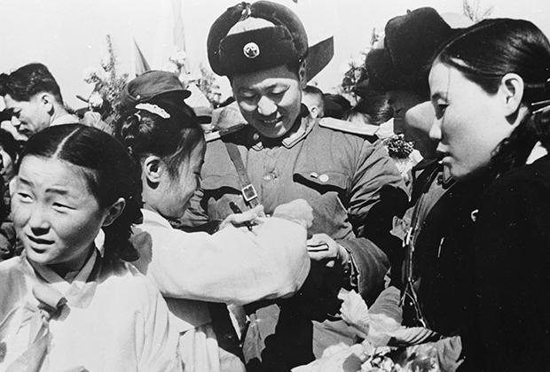 Корейская девочка дарит цветы уходящему из страны китайскому солдату. 1958 год