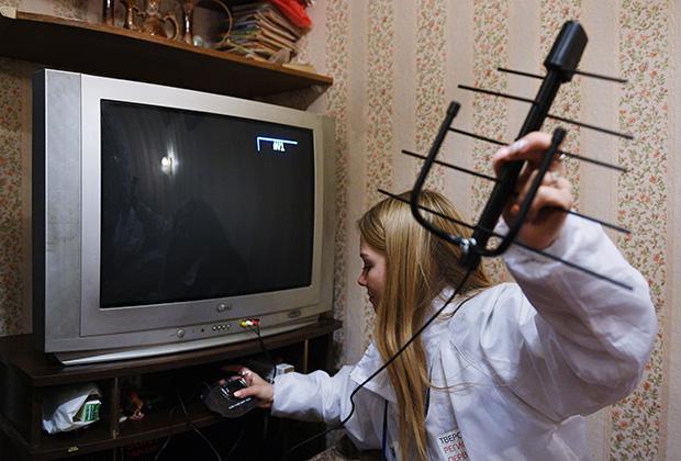Волонтер помогает настроить работу телевизора с приставкой для цифрового вещания для жителя Твери.