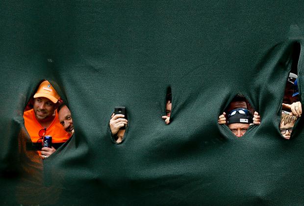 Фанаты гольфиста Тайгера Вудса наблюдают, как их кумир забивает мяч в 18-ю лунку в финальном раунде турнира Valspar Championship.