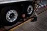 Греческий полицейский просит вылезти из-под грузовика мигранта, пытающегося нелегально проникнуть на паром, направляющийся в Италию. Офицер из отряда специального назначения береговой охраны встал на колени, чтобы осмотреть грузовик, который готовился заехать на паром. Внезапно он закричал: «Ложись! Выметайся отсюда!» Растерянный мужчина выполз, осмотрелся и молча сдался. Это был один из сотен молодых афганцев и пакистанцев, живущих на заброшенных фабриках напротив порта города Патры.  <br> <br> «Каждый день они перебегали через оживленную улицу к забору в поисках грузовиков, чтобы спрятаться. Большинство из них обнаруживали полицейские собаки и рентгеновские аппараты. Их удерживали в течение ночи и освобождали. Почти все будут испытывать свою удачу снова и снова», — считает фотограф, ставший очевидцем.