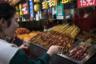 Улица Ванфунцзин — одна из самых популярных торговых улиц Пекина, знаменитая в том числе своим стритфудом. Здесь можно найти блюда из всех регионов Китая. Например, женщина на фото выбирает чуань —уйгурский шашлык. Маленькие кусочки говядины нанизывают на шпажку, обваливают в специях (тмин, кунжутное масло и хлопья сушеного перца) и жарят на углях.