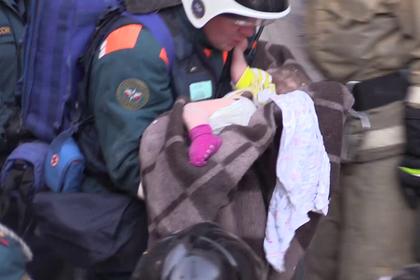 Извлеченный из-под завалов ребенок на руках спасателя