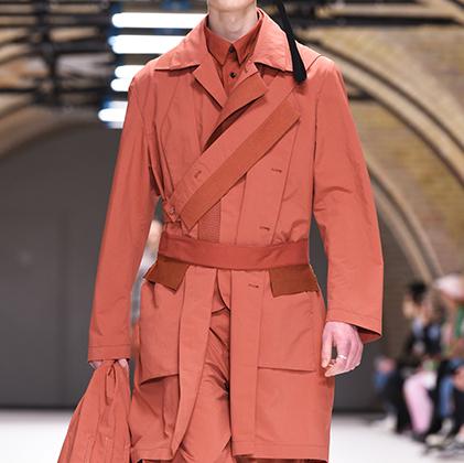 Тренч и брюки работы Крейга Грина выглядели бы вполне конвенционально, если бы не странные аксессуары с кисточками и не самый распространенный в мужском гардеробе терракотовый оттенок.