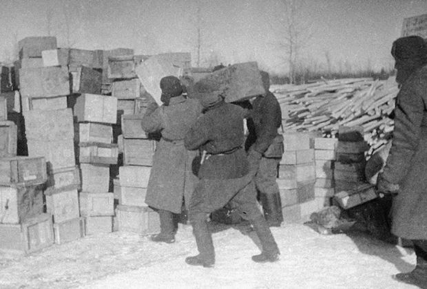 Солдаты разгружают ящики с продовольствием на складе на Ладожском озере во время блокады Ленинграда