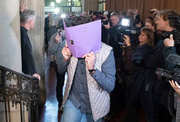 """A defendant covers his face when arriving at the court in Berlin, Germany, Thursday, Jan. 10, 2019 for the first day of the trial over the brazen theft of a 100-kilogram (221-pound) Canadian gold coin from a Berlin museum. The """"Big Maple Leaf"""" coin, worth several million dollars, was stolen from the Bode Museum in March 2017."""