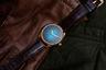 """Хитом бренда на SIHH были «дикие» <a href=""""https://lenta.ru/news/2019/01/10/plesen/"""" target=""""_blank"""">часы</a>, поросшие травой. Но и в обычных часах марка знает толк. Абсолютно лаконичная классика в корпусе из белого или красного золота с градиентным синим циферблатом оттенка Blue Lagoon. Ни часовых меток, ни цифр, ни логотипов. Часы оснащены автоматическим механизмом калибра HMC 200."""