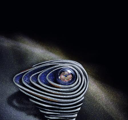 Часы-браслет из белого золота, полностью покрытые паве из бриллиантов и синих и оранжевых сапфиров (более 12 тысяч камней общим весом 66,10 карата) с кварцевым механизмом калибра 2710 больше похожи на украшение инопланетной принцессы. Сходства добавляет скрытый павированный сапфирами шар со сдвижной полусферой, скрывающей циферблат.