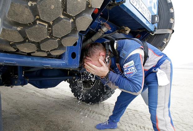 В машинах температура обычно очень высокая, поэтому пилоты используют любую возможность, чтобы освежиться. На этом снимке Эдуард Николаев из команды «КАМАЗ Мастер» умывается во время остановки.