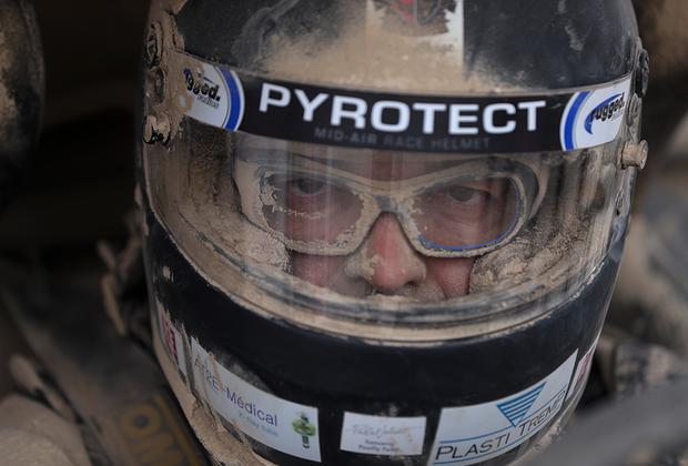 Так они и гонят километр за километром в грязи, дышат пылью и песком. Клода Форнье из Франции фотограф поймал во время дозаправки. Надетые под шлемом очки почти не спасают от всепроникающей пыли.