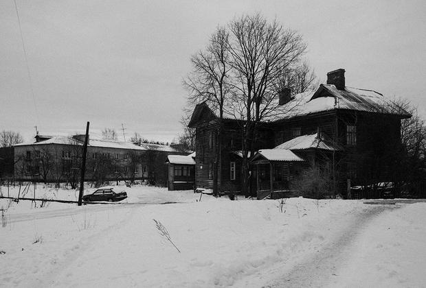 Валентина Максимовна живет в старом здании, сохранившемся со времен войны и пропитанном ее духом. Оно вот-вот рухнет, так как находится в аварийном состоянии. На заднем плане — новый многоквартирный послевоенный дом.