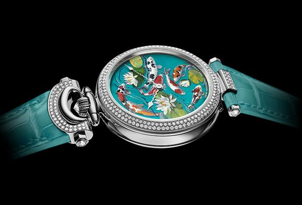 Фирменная система Bovet с трансформируемым корпусом Amadeo позволяет носить эти часы на запястье, а также как кулон или карманные. Китайских карпов в технике эмали grand feu на циферблате уникальной модели с автоматическим механизмом 11BA13 изобразил российский ювелир и эмальер Ильгиз Фазулзянов (он сотрудничает с брендом уже пятый год). Безель, дужки и ушко корпуса часов из белого золота павированы бриллиантами.